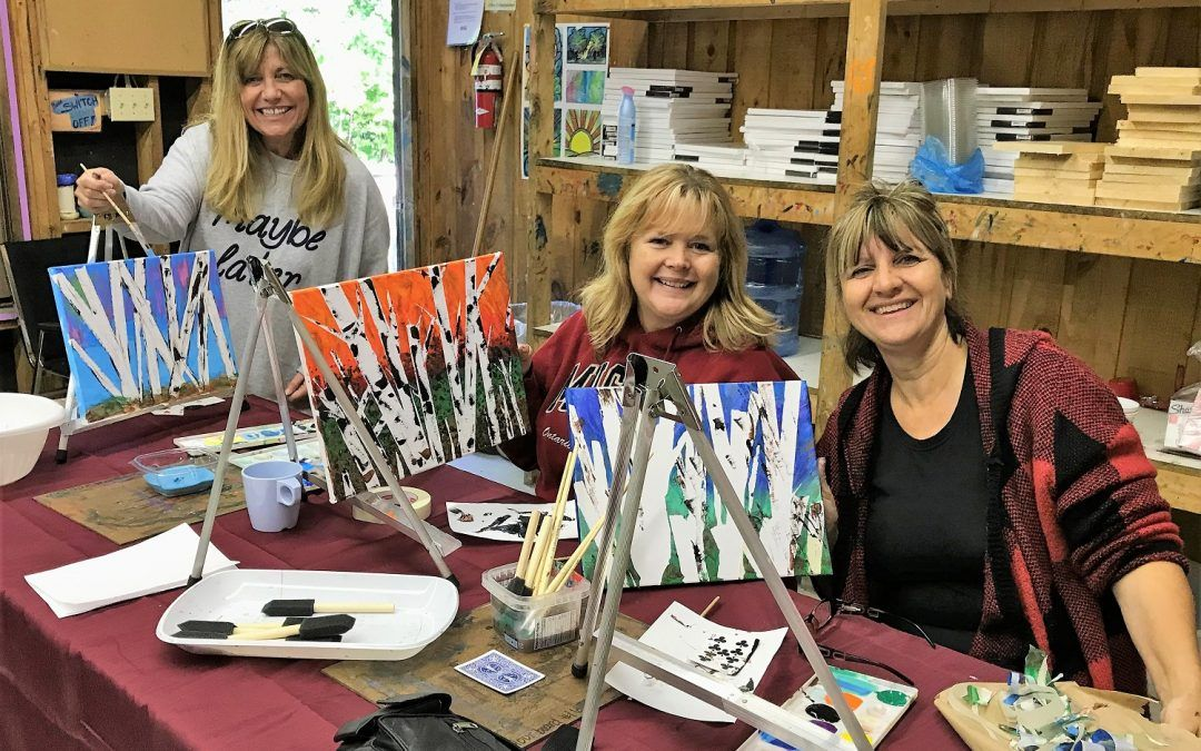 An image of participants painting at a Women's Weekend Retreat at Camp Wenonah in Muskoka Ontario.