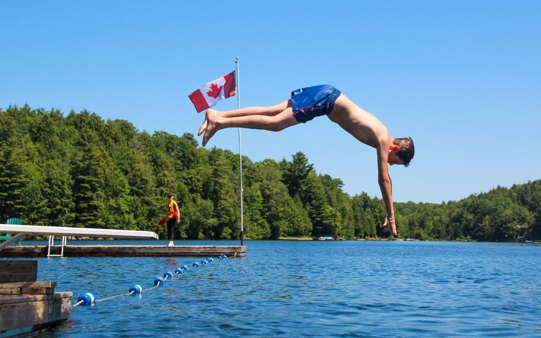 An image of a child diving into the water at Camp Wenonah in Muskoka Ontario